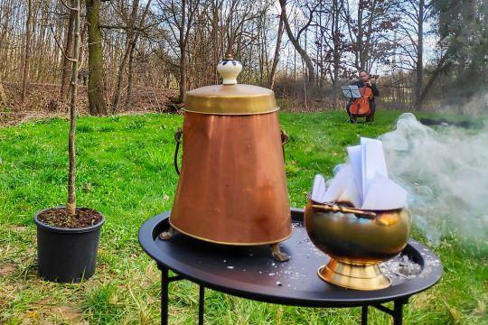 pohřební obřad: popel, pálení vzkazů, urna, violoncello, sázení stromu