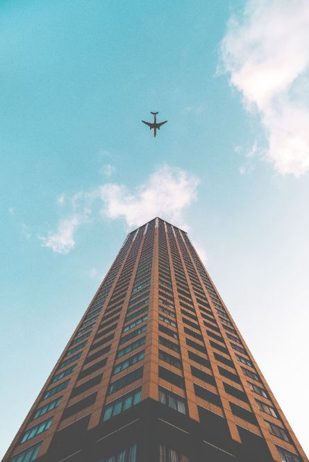 a plane flying above a high tower