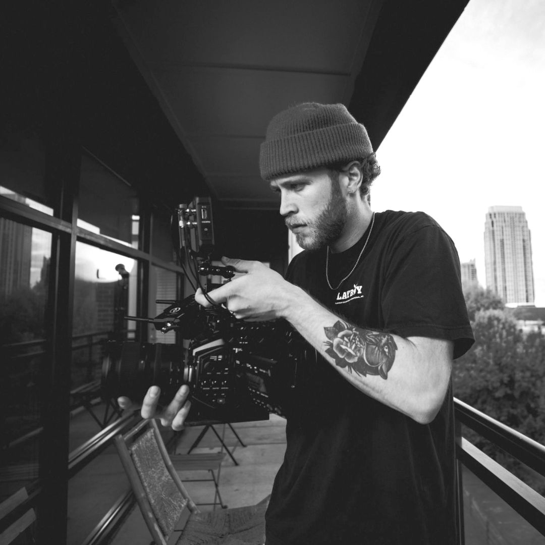 Gent mid 20's wearing a beanie hat, tattoo on his left arm showing whilst filming on a camera, skyscraper in the background.