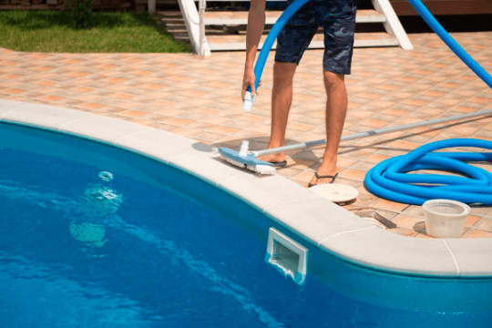 man adjusting pool brush